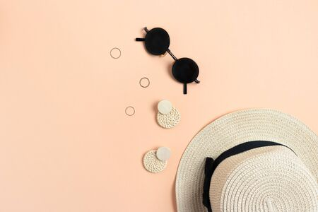Fashion flat lay. Straw hat, wicker earrings, golden rings, sunglasses on peach background.