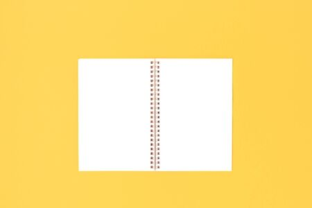 Blank copybook mockup on a bright yellow background. Clean template.