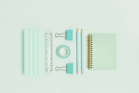 Set of office supplies on a mint pastel background. Monochrome creative concept. Imagens