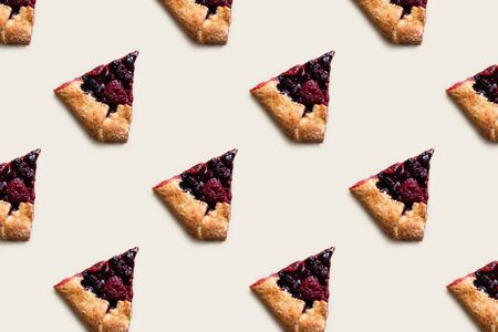 Pieces of homemade berry cake pattern on a beige background.