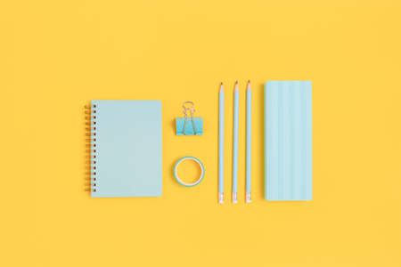 Group of mint color stationery on a bright yellow background. School equipment layout. Фото со стока