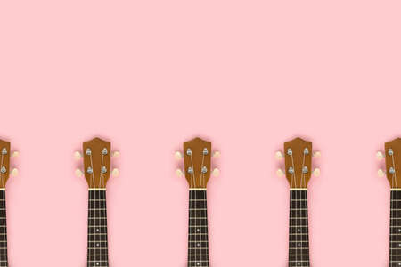 Frame made of guitar fretboards on a pink pastel background. Musical event invitation template.