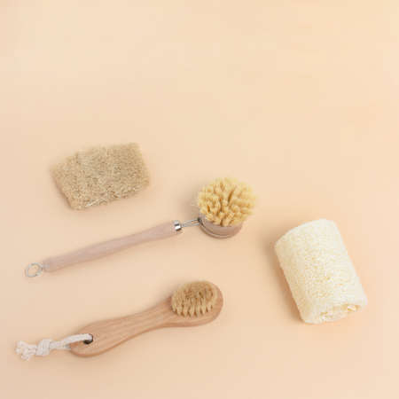 Layout of brushes made of bamboo and loofah on a beige background. Zero waste concept. Foto de archivo