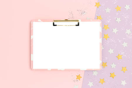 Blank clipboard mockup on a pink pastel background. Stars confetti texture. Festive glowing concept.