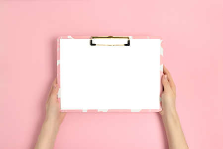 Female hands hold clipboard. Blank mockup on a pink pastel background.