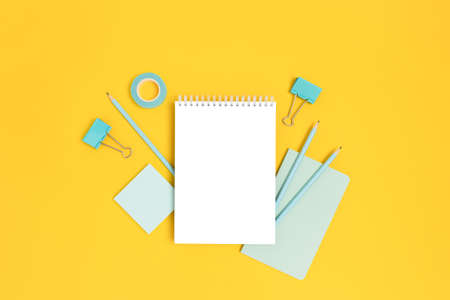 Notepad template with mint stationery on a bright yellow background. Creative mockup with copy space.