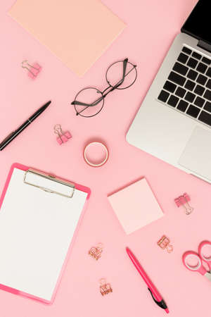 Top view of laptop and stationery on a pink pastel background. Creative student workspace. Banco de Imagens