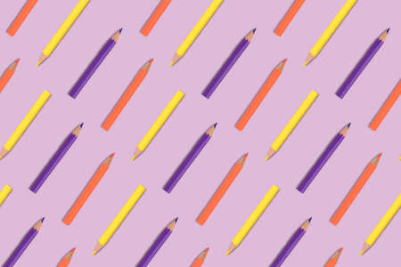 Color pencils pattern on a purple pastel background. Back to school layout.