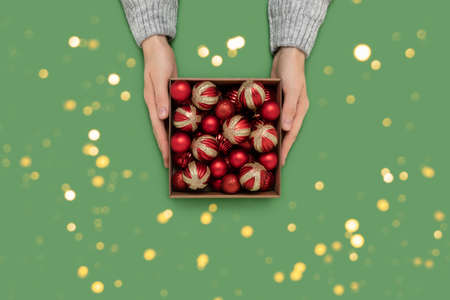 Female hands hold box with red Christmas baubles on a green background. Festive concept with golden bokeh. 写真素材