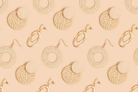 Different earrings pattern on a beige background. Monochrome fashion concept.