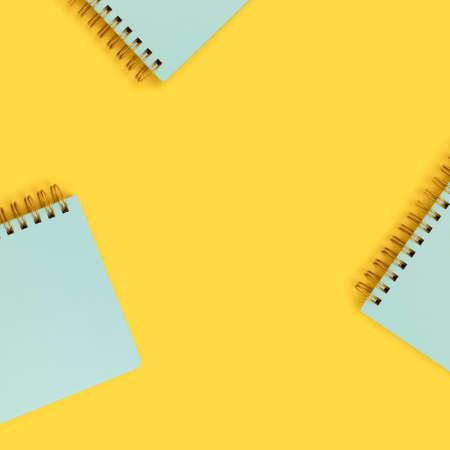 Frame made of mint spiral notepads on a yellow background. Cute school supplies. 免版税图像