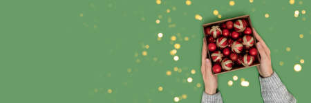 Female hands hold box with red Christmas baubles on a green background. Creative festive banner.