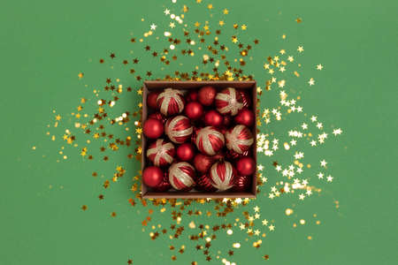 Box with red Christmas toys on a green background. Festive shiny composition with golden stars confetti.