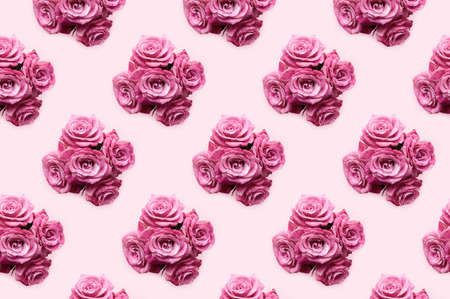 Pattern made from bouquets of rose flowers on a pink pastel background. Monochrome creative concept.