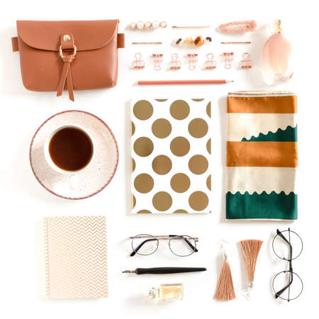 Flatlay of stationery, notepads, mug of coffee, woman's cosmetics and accessories on white background