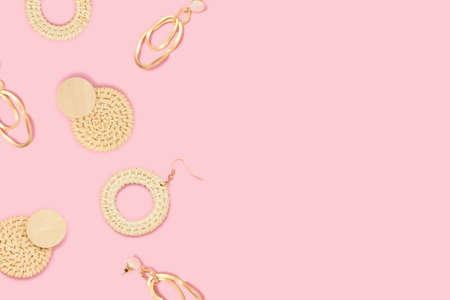 Earrings pattern frame on a pink background. Retro-style accessories with copy space.