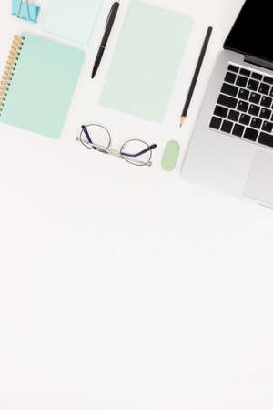 Workspace with laptop, glasses and stationery. White flatlay with copy space.