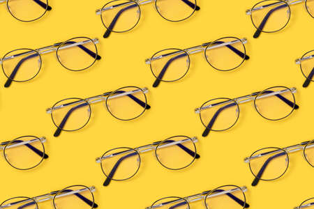 Eyeglasses pattern on a yellow background. Creative layout.