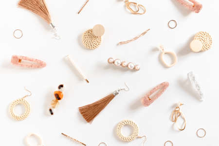 Pattern made of earrings, rings, hairpins on white background