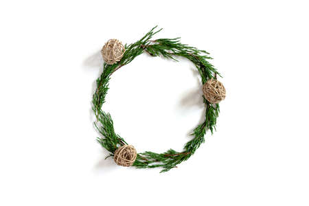Wreath made from conifer tree branches and rattan balls on a white background