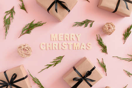 Pattern made of conifer tree branches, rattan balls, gift boxes packed in kraft paper tied with a black ribbon on a pink pastel background.