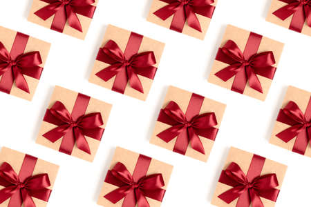 Repetitive pattern made of gift boxes tied with red ribbons on a white background. Holdays backdrop.