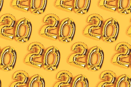 Numbers 20 golden balloons pattern. Twenty years anniversary celebration layout on a yellow background. Imagens