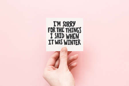 Minimal composition on a pink pastel background with girl's hand holding card with quote I'm sorry for the things I said when it was winter