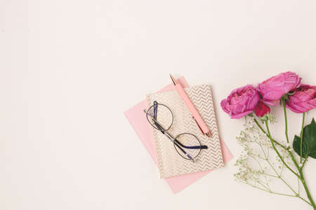 Feminine workspace with bouquet of flowers on a beige background. Layout of cute stationery and eyeglasses.