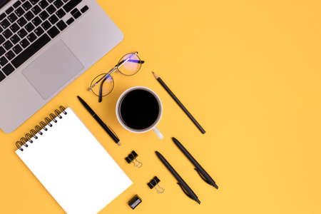 Organized workspace with coffee, laptop and office supply on a yellow background. Online education, remote job concept with copy space.