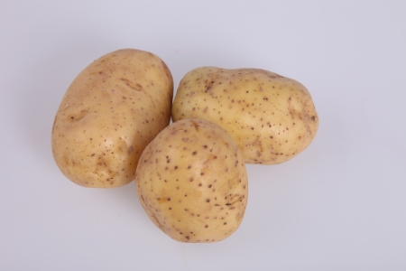 unpeeled: Three clean unpeeled potatoes on white background Stock Photo
