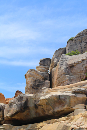 Top of a rocky cliff with blue sky in the background Stock Photo