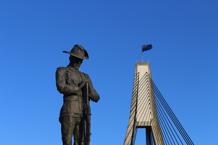 Anzac Day. Bronze statue of an Australian World War One Digger. The statue of the New Zealand soldier. Blue sky and the Anzac Bridge in the background. Remembrance Day.
