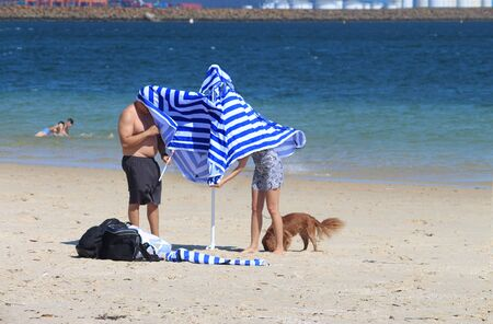 Funny photo of couple with heads under a beach umbrella trying to put it up Stock Photo