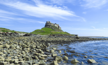 Lindisfarne Castle panoramic view from a rock beach and blue water, Holy Island, Northumberland, UK 版權商用圖片