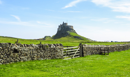 Lindisfarne Castle panoramic view, rock fence and wooden gate, Holy Island, Northumberland, UK 版權商用圖片