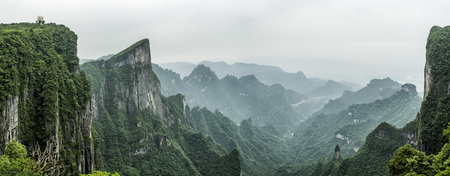 Tianmen Mountain Known as The Heavens Gate surrounded by the green forest and mist at Zhangjiagie, Hunan Province, China, Asia