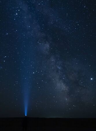 Torch light pointing to the Milky Way - Gobi Desert, Mongolia