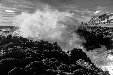b w images: A wave breaks violently and forcefully among the rocks Stock Photo