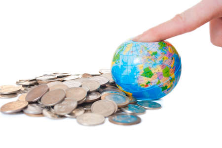 The man pressed his finger on a globe on the background of the money Stock Photo