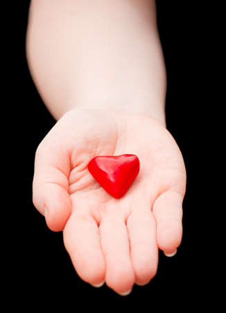 Plasticine heart in hand on a black background Stock Photo - 13006956