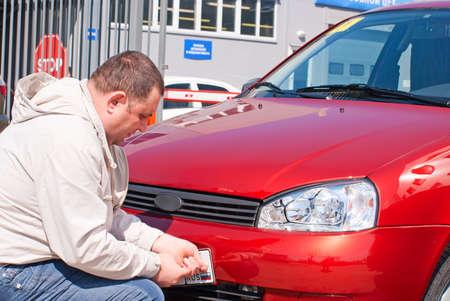 De mens hecht de serienummers van de gekochte auto