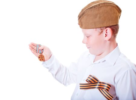 The boy is holding a medal on a white background