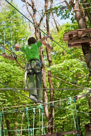 Een jongen overwint hindernissen, wandelen op een touw