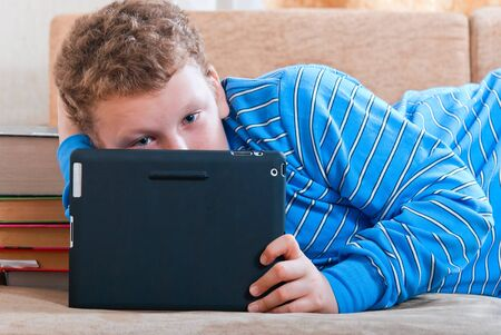 Boy with a tablet computer lying on the sofa photo