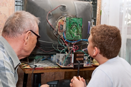 Grandfather and grandson are repairing an old TV