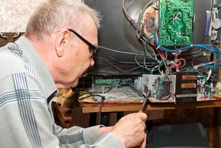 An elderly man repairing an old TV Stock Photo