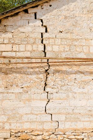 foundation cracks: A large crack in the wall of an old residential building