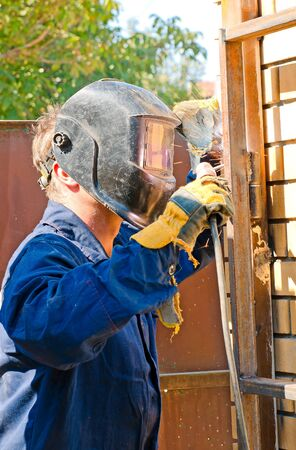 Welder in the mask during operations against the blue sky