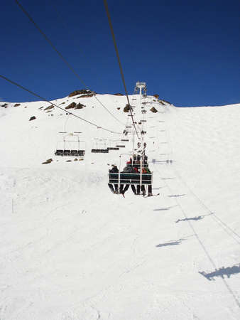 sitting in ski lift with snow mountain view and blue sky                             photo